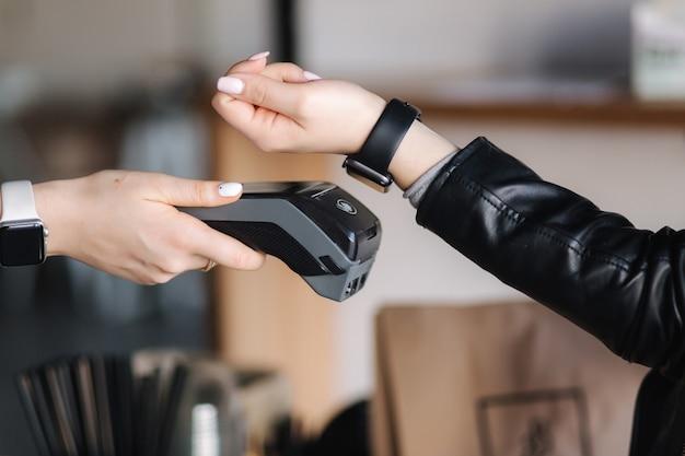 Клиентка-женщина делает беспроводные или бесконтактные платежи с помощью умных часов крупным планом человеческих рук