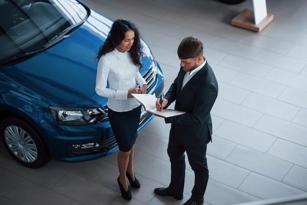 Cliente femminile e uomo d'affari barbuto elegante moderno nel salone dell'automobile