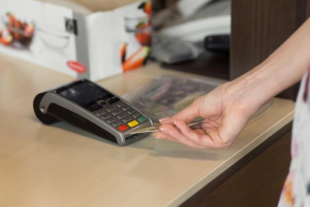 카페에서 신용카드로 결제하는 여성 고객. 신용 카드 판독기에 보안 핀을 입력하는 여성의 손에 초점을 맞춥니다.