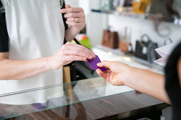 Female customer paying for purchase by credit card in clothes store, giving blank card to cashier over desk. cropped shot, closeup of hands. shopping or purchase concept