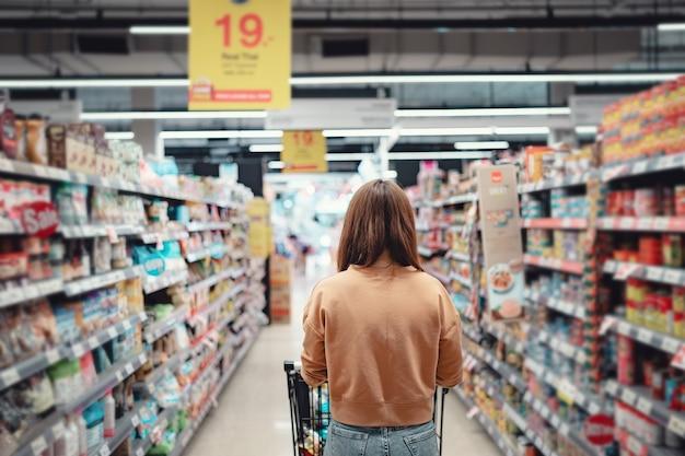 トロリーでスーパーマーケットで買い物をする女性客