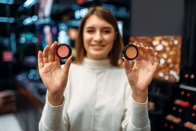 女性客は化粧品店で化粧品を示しています。