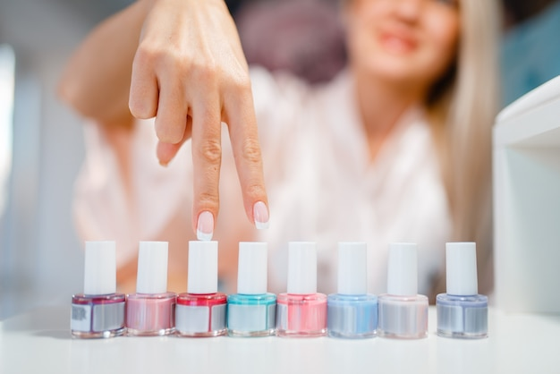 Female customer shows nail varnish choice in beauty shop.