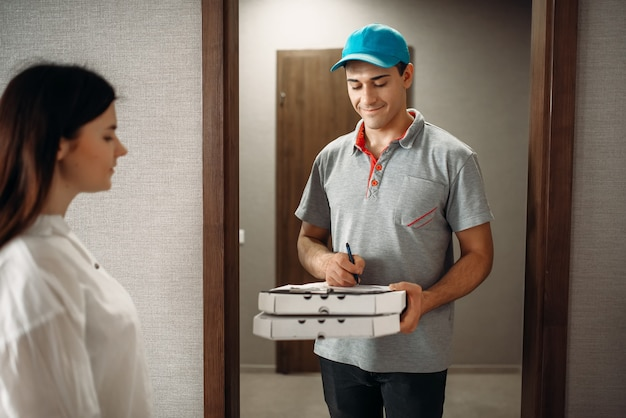 Female customer signs order to pizza delivery boy