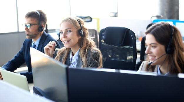 ヘッドセットと笑顔で、バックグラウンドで同僚と女性のカスタマーサポートオペレーター。