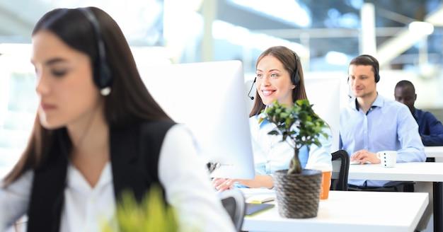 Оператор службы поддержки клиентов женского пола с гарнитурой и улыбкой, с коллегами на заднем плане.