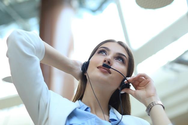 Оператор службы поддержки клиентов женского пола с гарнитурой и улыбается