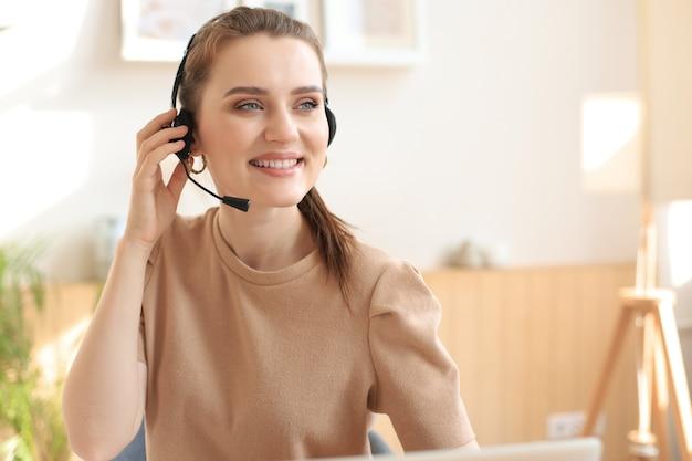 Оператор службы поддержки клиентов женского пола с гарнитурой и улыбается.