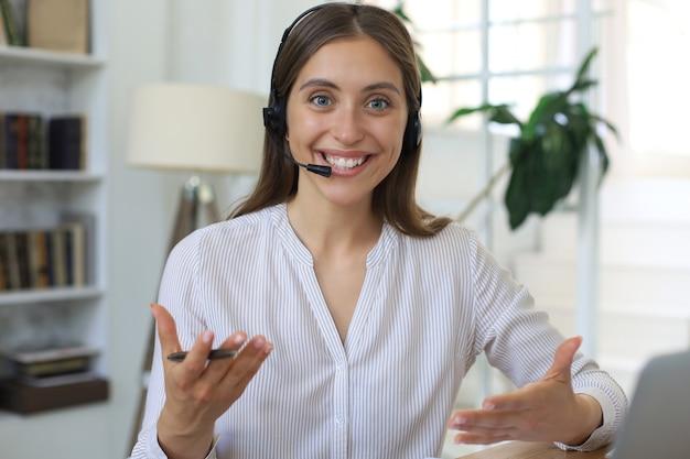 Оператор службы поддержки клиентов женского пола с гарнитурой и улыбается. Premium Фотографии