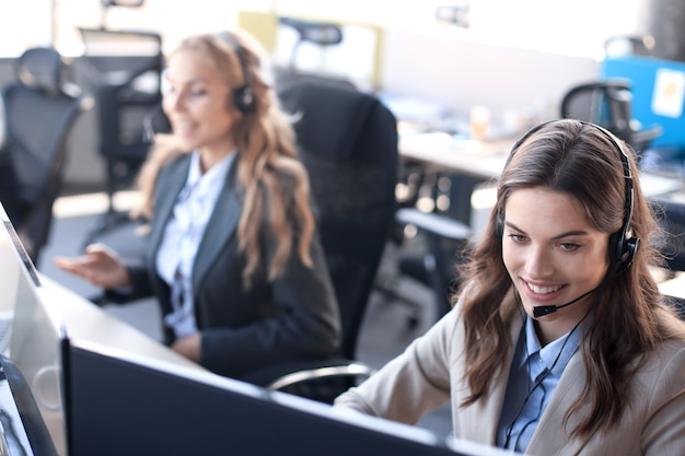 Female customer support operator with headset and smiling, with collegues at background.