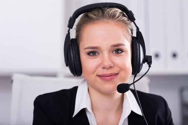 Female customer support phone operator at workplace