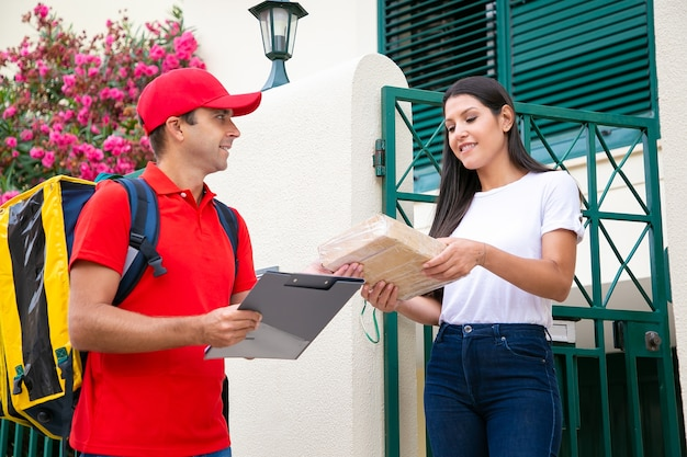 양손으로 택배에서 소포를 복용하는 여성 고객. 빨간색 유니폼을 입고 여자에게 주문을 전달하는 노란색 열 배낭과 함께 행복 배달원. 택배 서비스 및 포스트 개념