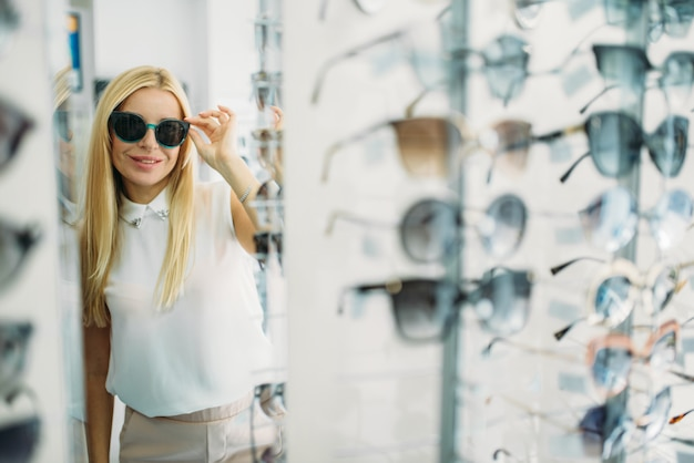 Female customer tries on sunglasses in optics store, showcase with spectacles