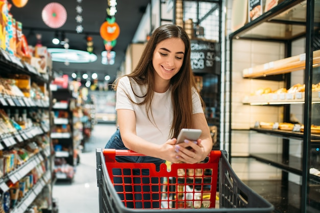 Покупательница использует мобильный телефон в супермаркете