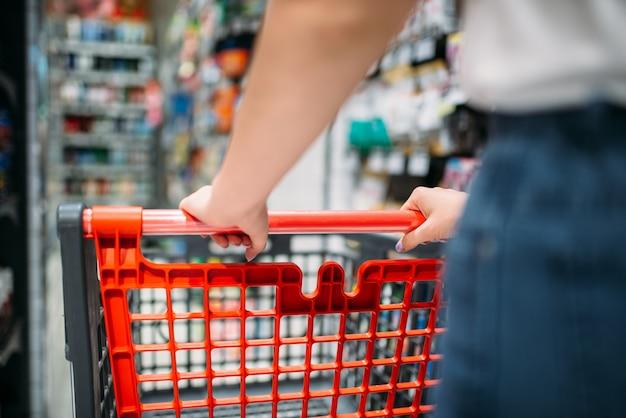 Клиентка с тележкой в продовольственном магазине, вид сзади. женщина, делающая покупки в продуктовом магазине