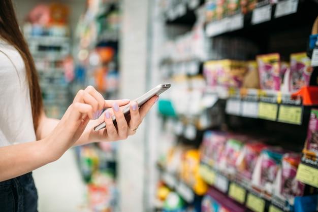 Клиентка с телефоном в руке, продуктовый магазин. женщина использует смартфон в продуктовом магазине