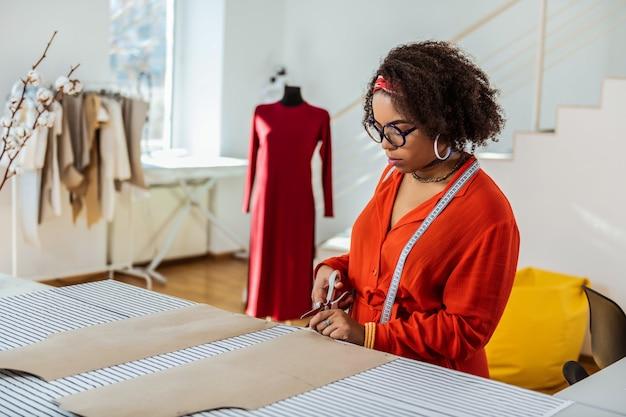 女性のカッティングペーパー。作業台の近くに滞在しながら衣装のモデルを作成する集中的な魅力的な女性デザイナー