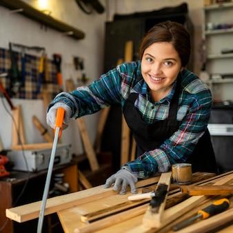 Female cutting a wood plank