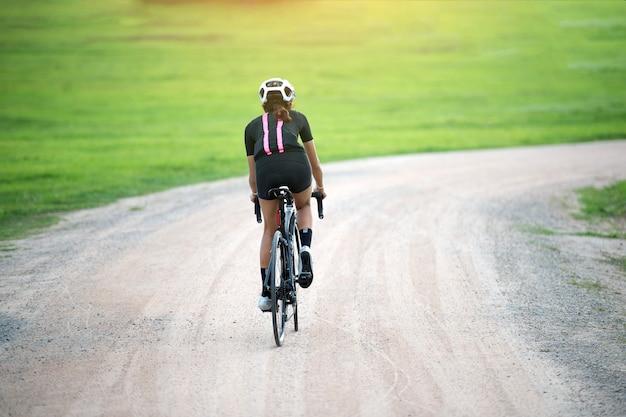 田舎の未舗装の道路でサイクリングの女性