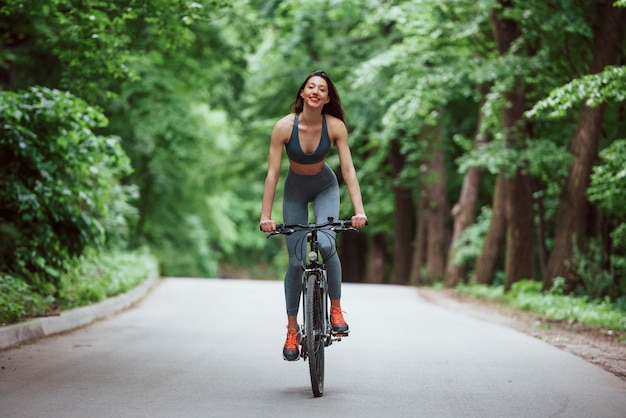 Female cyclist on a bike on asphalt road in the forest at daytime