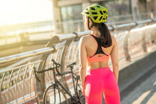 女性サイクリスト。橋に立っているピンクのレギンスの女性サイクリスト