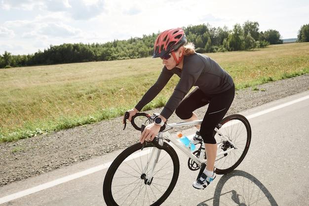 스포츠 의류와 헬멧을 쓴 여성 자전거 타는 사람이 도로에서 경주용 자전거를 타고 있습니다.