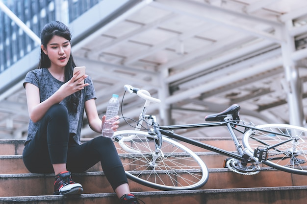 Female cyclist is relaxing drinking water on a stair