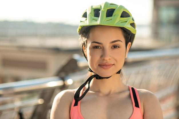 女性サイクリスト。保護ヘルメットのきれいな女性サイクリストの肖像画の写真