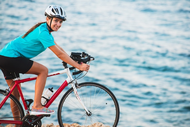 Female cyclist riding bike with sea