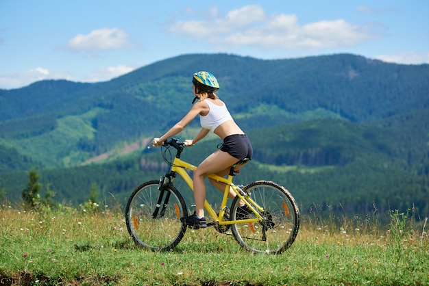 Female cyclist riding on yellow bicycle