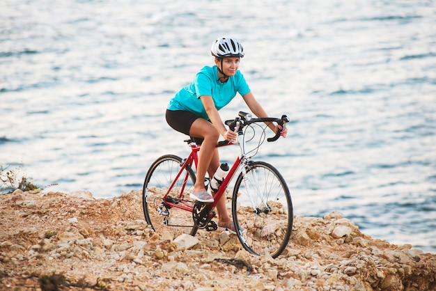 Female cyclist standing on a rock with bike and looking at sea