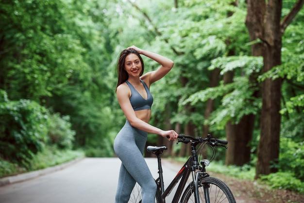 Велосипедистка, стоя с велосипедом на асфальтовой дороге в лесу в дневное время