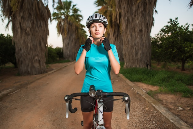 Female cyclist wearing helmet on path with palms