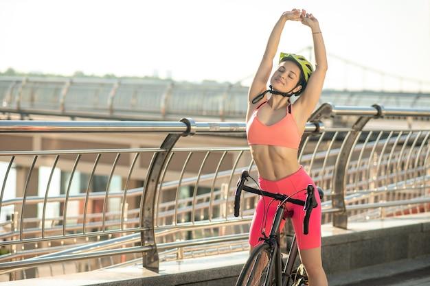 女性サイクリスト。レーシングバイクの明るいスポーツウェアの若いサイクリスト