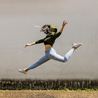 Female dancer in hood jumping against wall