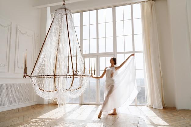 복도에서 샹들리에 근처 흰 드레스 여성 댄서