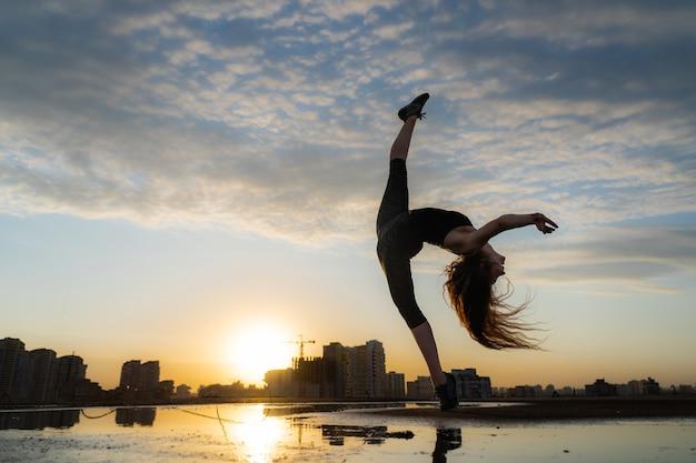 Танцовщица показывает свою гибкость во время заката на городском пейзаже с отражением в воде концепции свободы и счастья
