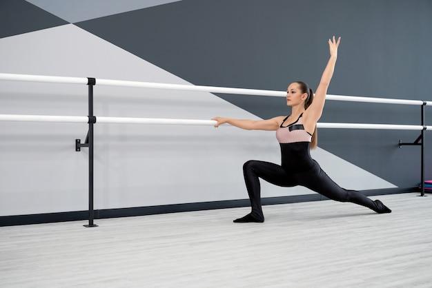 Female dancer stretching in ballet studio