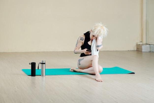 Танцовщица вытирает пот и проверяет социальные сети на смартфоне после тренировки