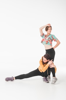 Female dancers dancing against white background