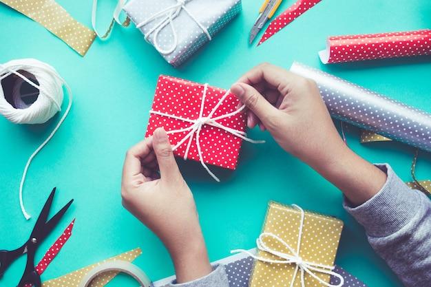 女性がかわいいギフトボックスを飾る作業台、フラットレイにプレゼント