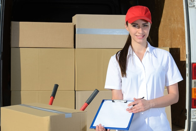 Female delivery driver with clipboard and box.