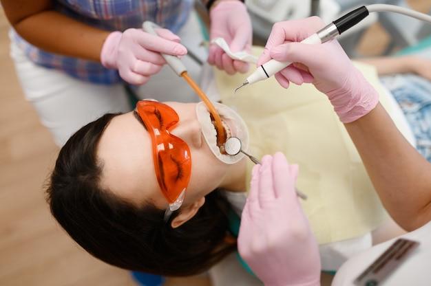 Женский стоматолог и ассистент лечит пациента в клинике, стоматологии