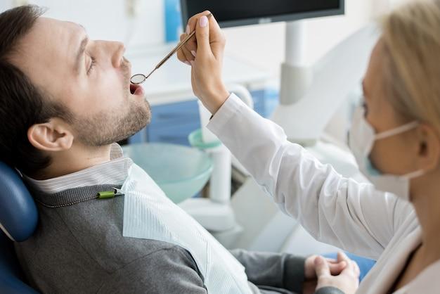 Female dentist examining patient