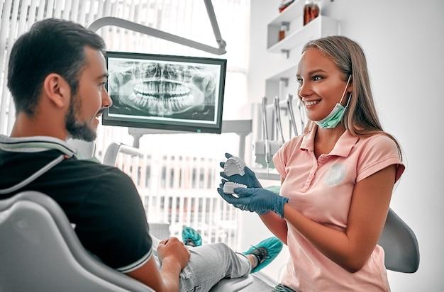 クリニックオフィスで患者に見せて説明する歯のモデル義歯を保持している女性歯科医、ヘルスケアの概念。口腔衛生のデモンストレーション。