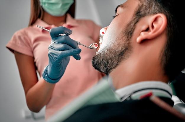 치과 진료소에서 도구로 환자를 검사하는 마스크를 쓴 여성 치과의사. 치과의사 의자에 있는 남자의 치아에 치과 치료를 하는 의사.