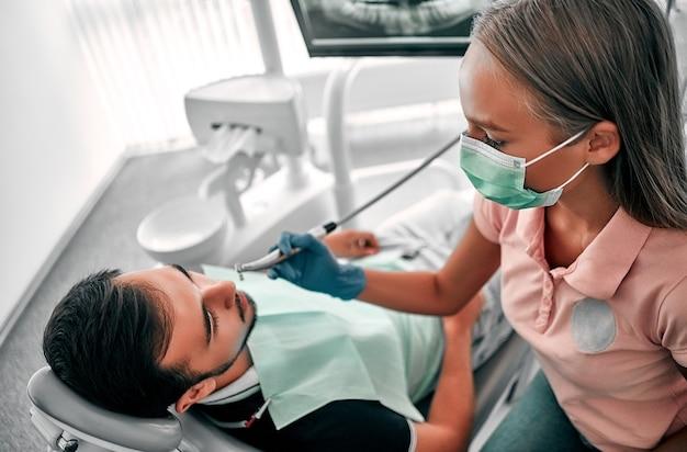 마스크를 쓴 여성 치과의사는 치과에서 드릴로 치아를 치료합니다. 치과의사 의자에 있는 남자의 치아에 치과 치료를 하는 의사.