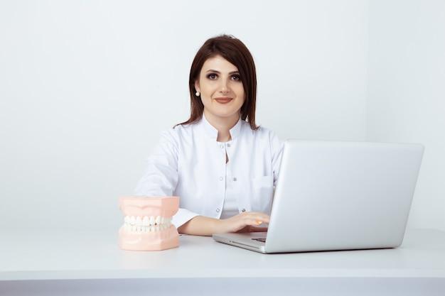 Женский стоматолог в форме сидит за столом и работает со стоматологическим персоналом в офисе.