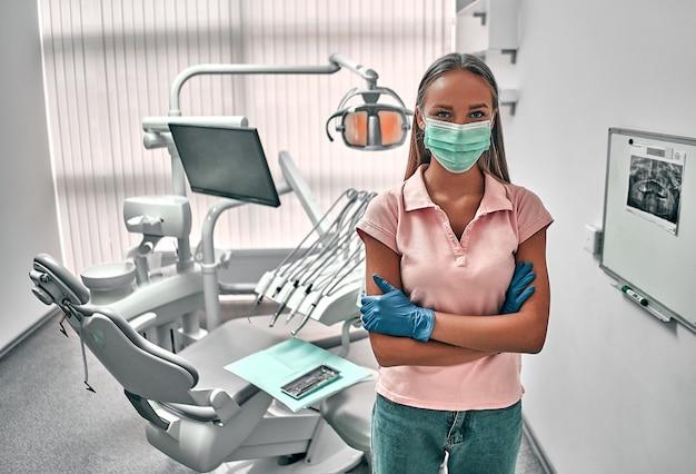 여성 치과의사는 현대적인 구강 클리닉에서 일하고 있습니다. 치과 진료소의 구강 기구. 의학, 건강, 구강학 개념입니다.