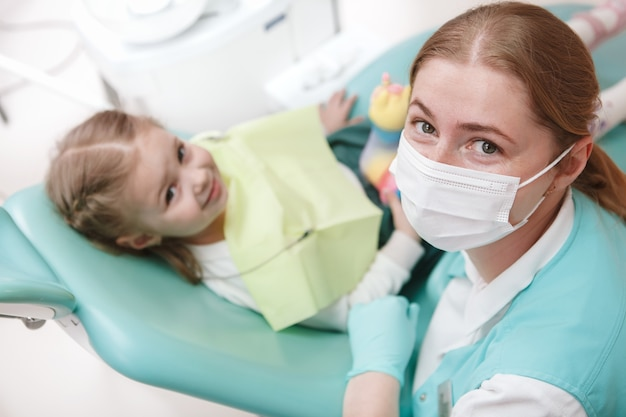 Female dentist in medical face mask looking to the camera while working with a child